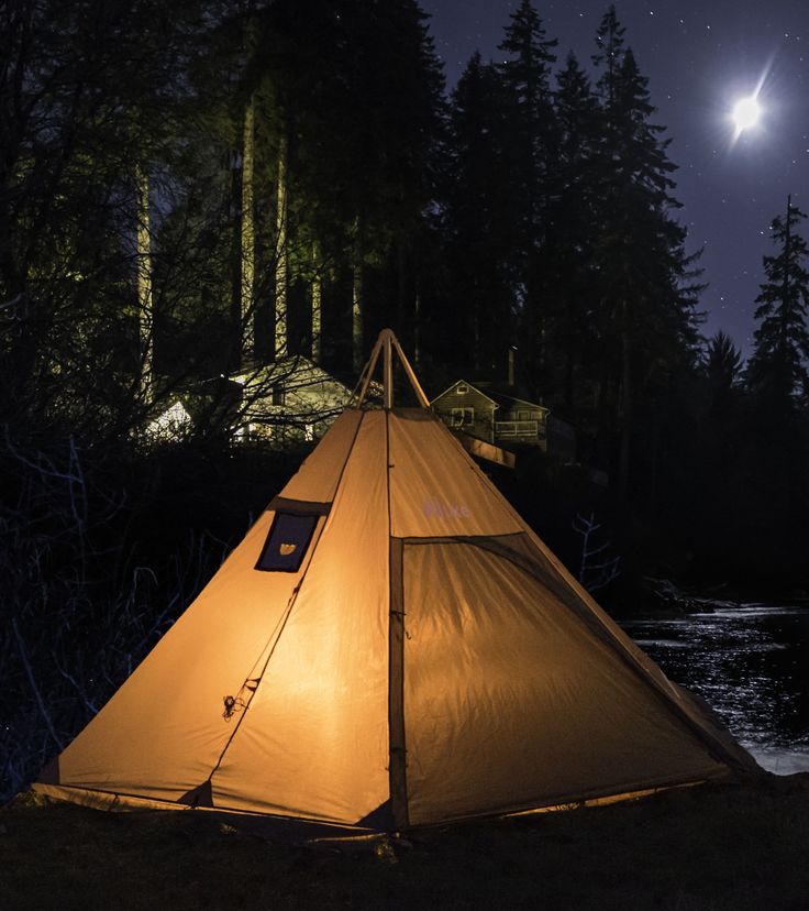 Wood fire camp stove inside teepee tent with removable chimney cap