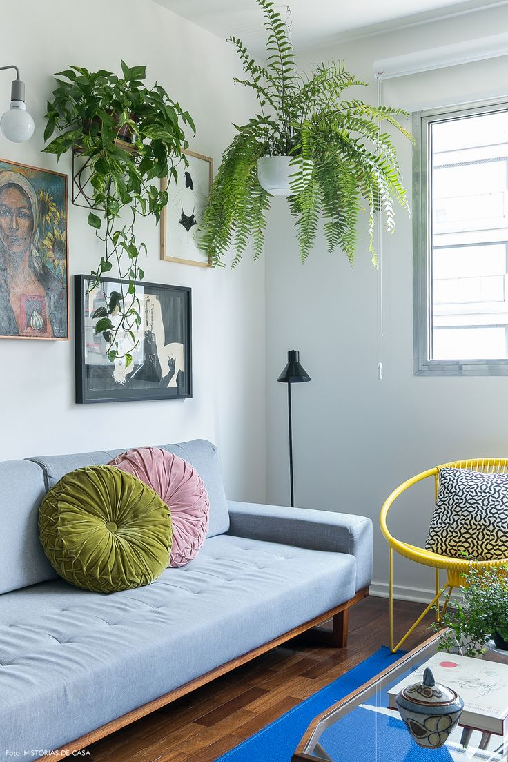 Poltrona amarela, tapete azul e parede galeria na sala de estar desse apê.