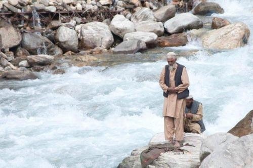 Offering prayer (salat) beside a rushing river. Beautiful image of devotion.