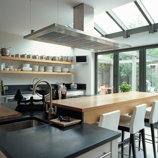Modern bistro-style kitchen extension  Skylights and a statement extractor fan give this sleek kitchen-diner the wow factor. A breakfast bar has been added to the central island unit, making it a great place for the family to catch up.