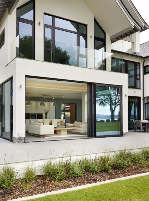 Large sliding doors open from the kitchen open on to a lovely patio area. Perfect for summer days and alfresco dining. Indoor - outdoor living inspiration. Lympstone Project | Sapphire Spaces - bulthaup b1 Kitchen