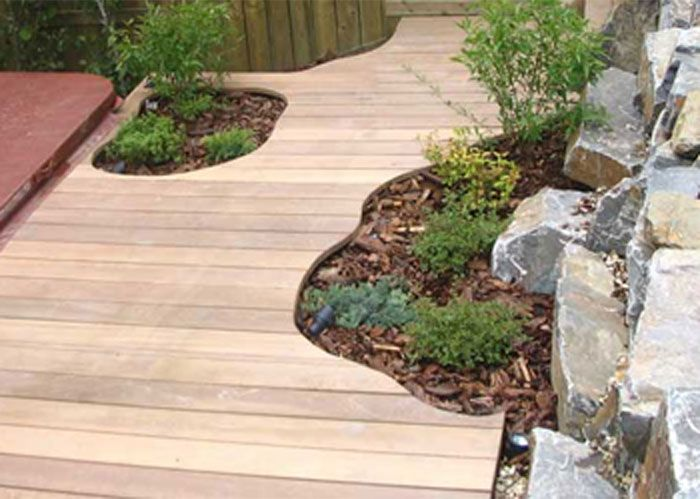 CREATE ESCAPE - Mount Royal.  Hardwood decking with custom cut edges for plantings. Sunken hot tub to enjoy a smaller space. Kootenay Brown Stone retaining wall.