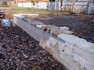 Stone seating wall with cinder block and stone fa ade for How to build a concrete block wall foundation
