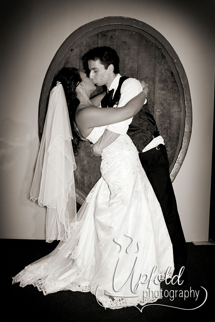 Bride and groom dip-and-kiss photo. This was taken in front of one of the wine barrels at Langtons On Lincoln, in Henderson. Image by Upfold Photography, Auckland, NZ www.upfoldphotography.co.nz. ~ black and white photography ~