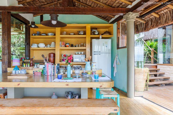 Mesa de madeira, banquinhos de palha e armário de alvenaria pintado de amarelo.