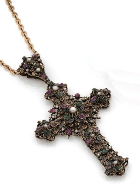 CROIX-PENDENTIF en argent, ajouré de feuillages stylisés, serti de rubis, d'émeraudes, de perles et de pierres de couleurs dans des motifs émaillés, retenu par une chaîne en or jaune 18K . Travail austro-hongrois du XIXe siècle pour la croix. H_12,5 cm environ. Poids brut total: 55,6 g