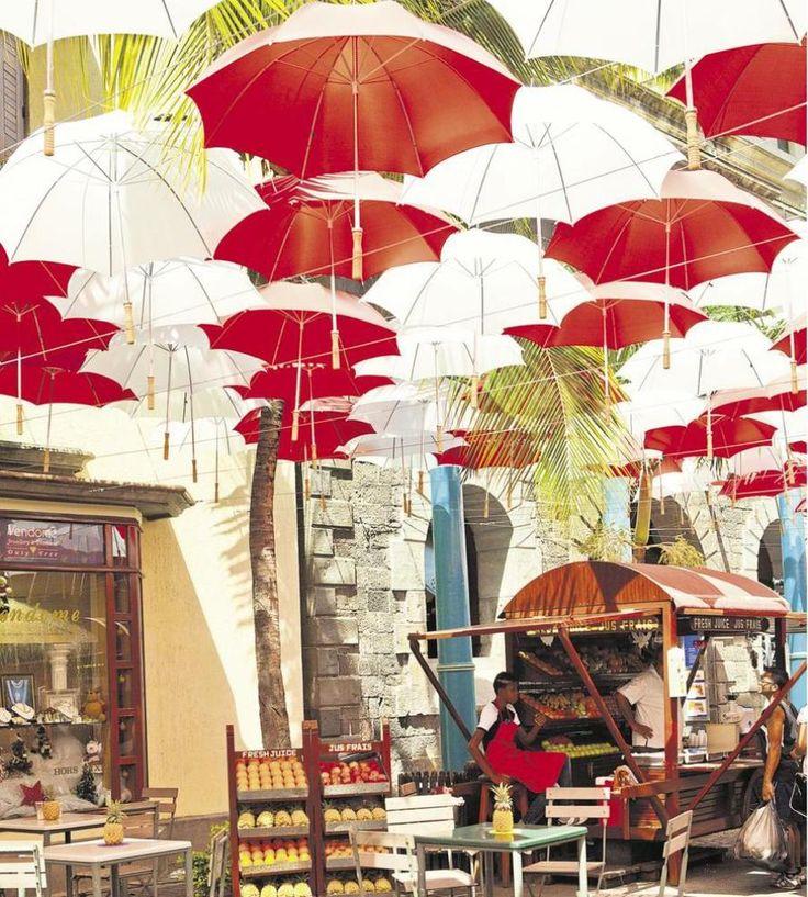 Mauritius | 'n Baldakyn van sambrele begroet toeriste by die waterfront op pad na die handwerkmark.