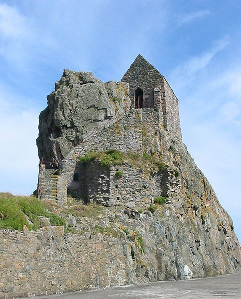 A medieval chapel. The hollow in the rock is where St. Helier sheltered. The Hermitage rock is the focus of annual pilgrimage. Saint Helier is a 6th century ascetic hermit. He is the patron saint of Saint Helier, Jersey Island's capital.