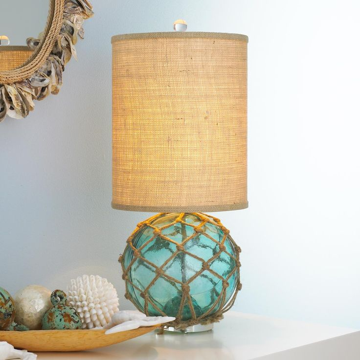 Modern Buoy Glass Table Lamp A modern twist on a vintage find explains the combination of styles wrapped up in this table lamp. The vintage glass buoy with rope netting sits on an acrylic base and topped with a modern shaped cylinder burlap shade. The look is clean and up to date nautical. Each base will vary slightly in size and color due to the one-of-a-kind nature of the vintage glass buoy.