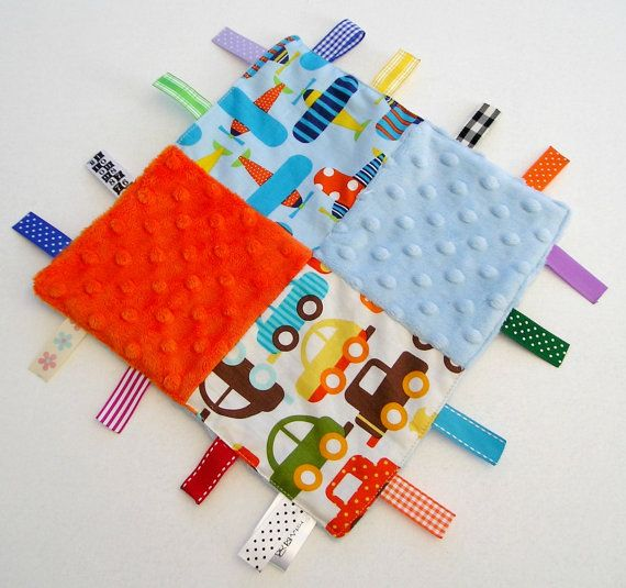 This beautiful ribbon sensory blanket is perfect for hugging. It measures approx 9.5 inches square (not including ribbons).  It is made with soft textured minky dot fabric, cotton fabric and ribbon. The front is a patchwork of cars, planes, blue and orange minky dot fabric. There are 16 ribbons in different colours around the edge which are heat sealed. One ribbon is looped to allow you to hang the taggie on a plastic ring. The minky fabric is soft to cuddle and the ribbons are great for…