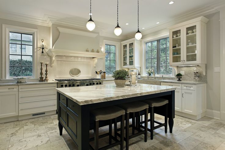 Large white and bright kitchen with large dark wood kitchen island. Several windows throughout provide plenty of natural light