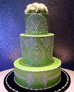 Round three tier green wedding cake decorated with intricate and elaborate white artwork
