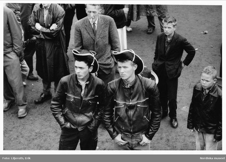 Kiviks marknad, Skåne. Två unga män i skinnjackor och cowboyhattar står i en grupp människor. Ca 1957-1967