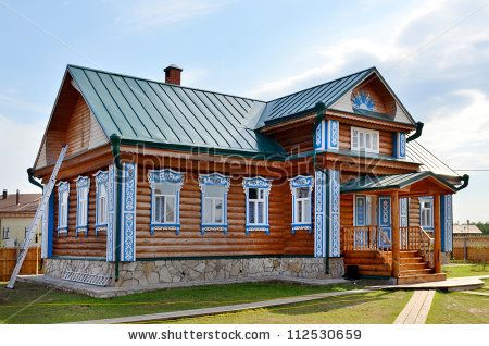 Traditional russian rural wooden house with carved porch - stock photo