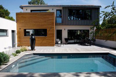 Une piscine familiale pour une maison design. Cette piscine a reçu le trophée d'or dans la catégorie piscine familiale de forme angulaire.      Sas Lermite - Caron piscines  Descriptif produit : Modèle : classique avec escalier angle intérieur et volet intégré sous terrasse. Dimensions : 3,50m x 7m. Matériaux : 100% béton. Caractéristiques techniques particulières : volet intégré sous terrasse. Revêtement : PVC liner 75/100 gris anthracite. options : nage à contre-courant, LEDS couleur.