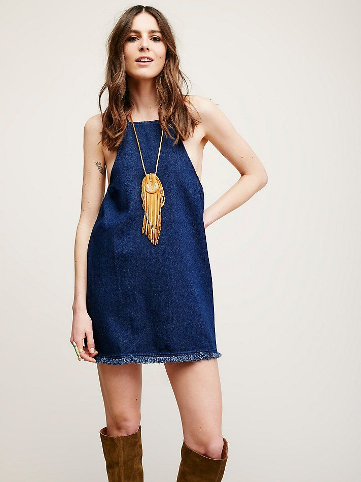 Lace Up Back Denim Tunic | Sleeveless denim tunic featuring a lace-up detail in back with oversized metal grommets.  Elastic bands under the arms for an easy fit. Raw hem.