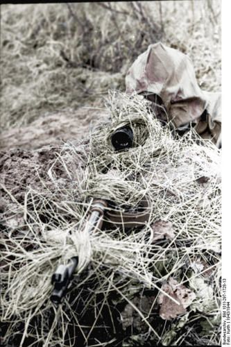 An photograph of a German sniper in Sumpftarn aiming through his riflescope.
