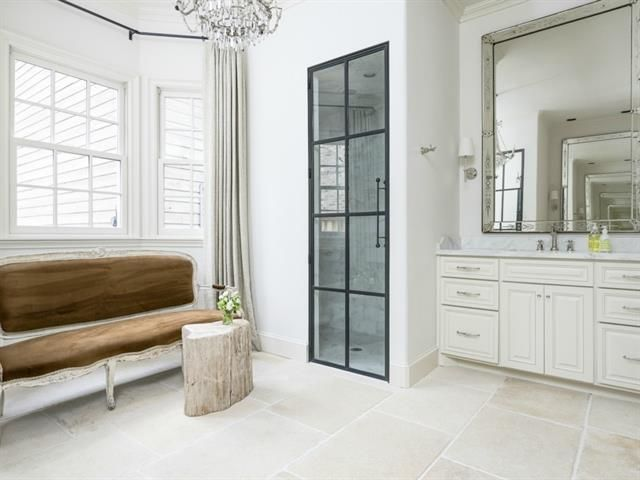 I like the shower door in this white bathroom with its long handle.