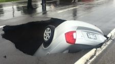 MyNews contributor sends in this image of a car almost completely swallowed by a sinkhole highway in