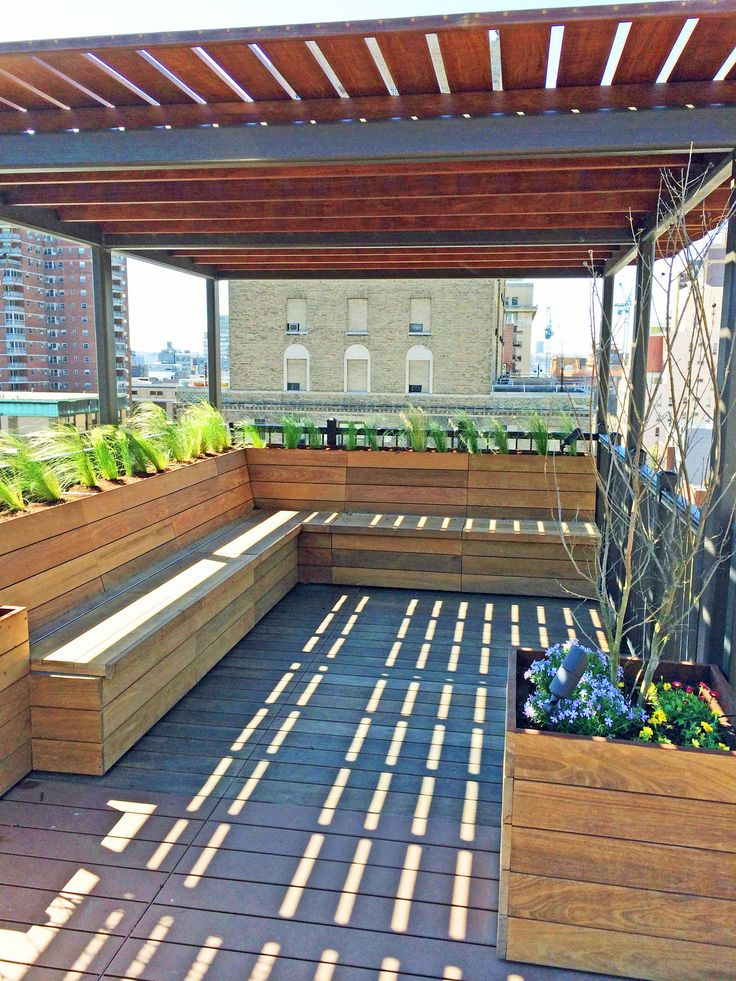 This custom roof deck overlooking Manhattan's Penn Station features lightweight aluminum decking, ipe planters, an ipe and metal pergola, and ipe benches with built-in storage under the seats.  Read more about this garden on my blog, www.amberfreda.com.