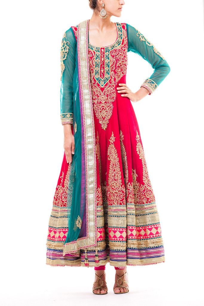 Hot pink velvet anarkali with teal green sleeves and gold zari embroidery and various borders.