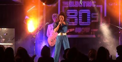80s blue satin jumpsuit and big, big hair. Electric 80s Show