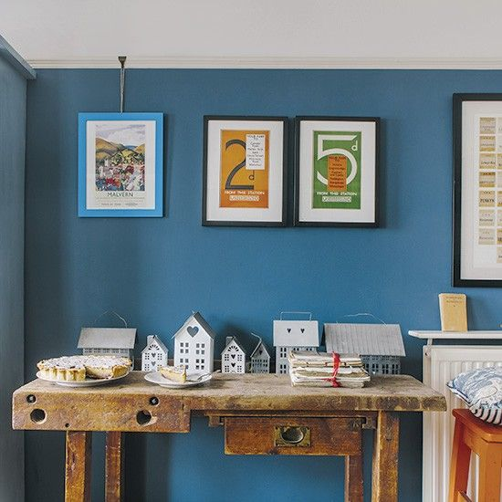 Blue home office with reclaimed workbench and prints