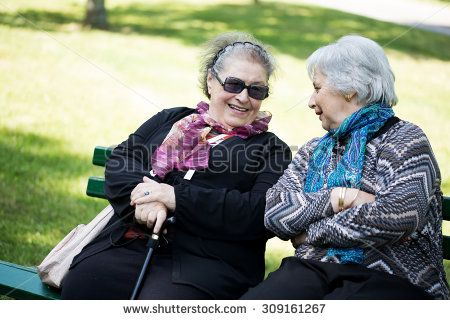 two senior ladies chatting friendly on a bench to the park - stock photo