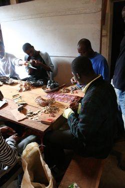 Assistants in El Anatsui's studio working with liquor bottle tops