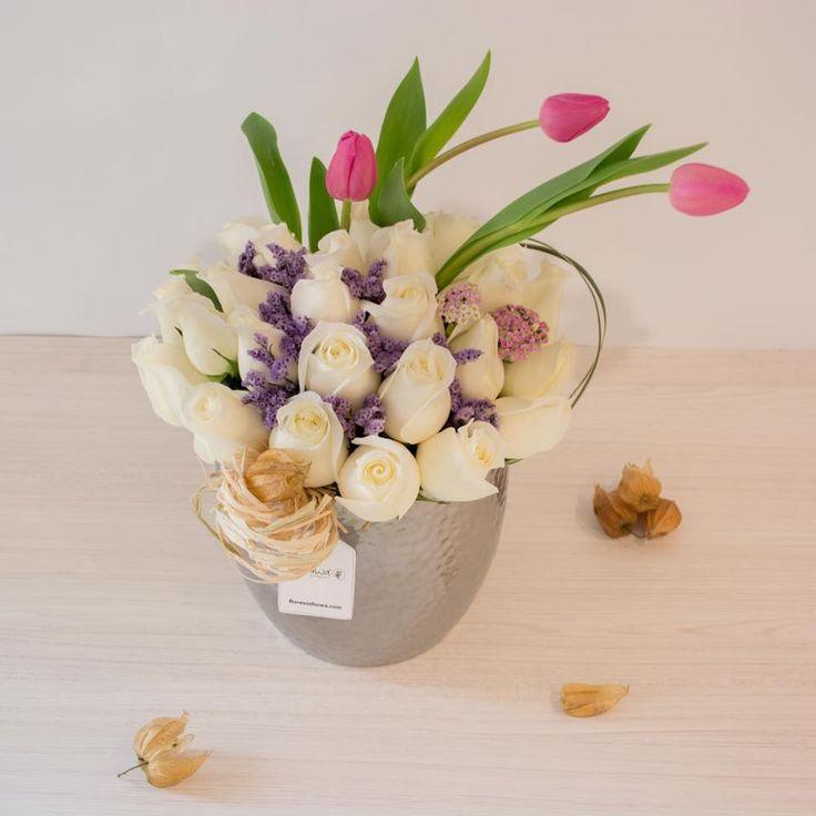 Rosas blancas mezcladas con tulipanes rosados.