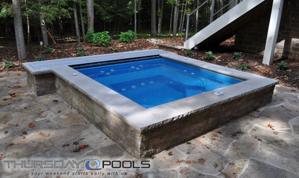 This spa project includes a raised rectangle 9 x 9 fiberglass spa with an automatic safety cover for One piece inground swimming pool