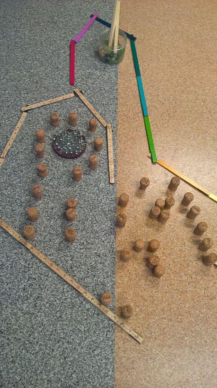 Lasten suunnittelema peli, materiaaleina pullonkorkit, marmorikuulat, taittomitat ja puukepit