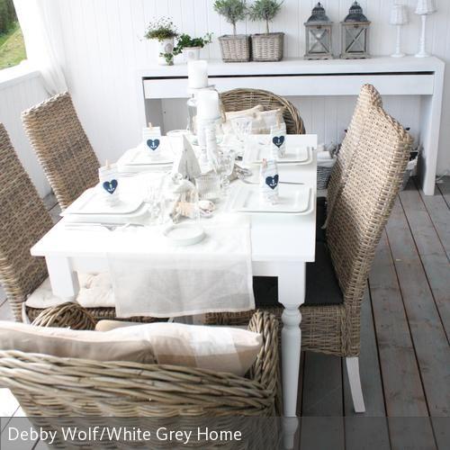 Auch der neue Esstisch mit den naturfarbenen Korbstühlen bietet noch genügend Platz für Freunde dekoriert mit blau-weiß gestreiften Servietten und viel weiß!