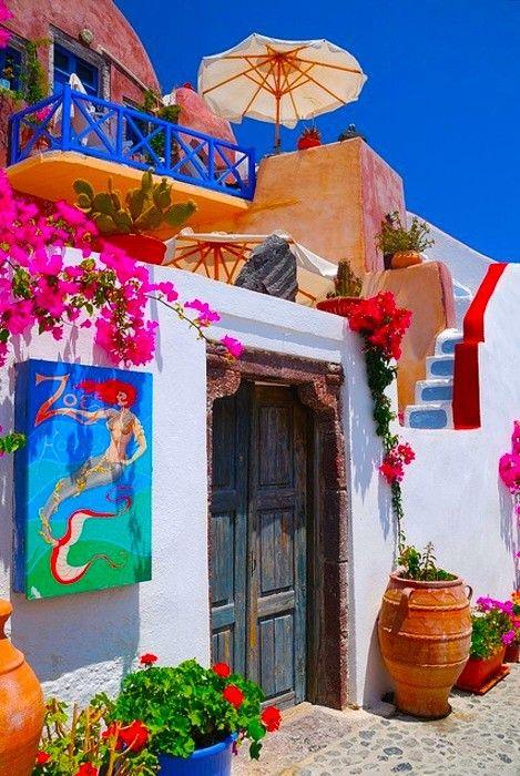 Le dan mucho color a la fachada usando todos esos colores tan vivos en flores, cuadro, varandal.