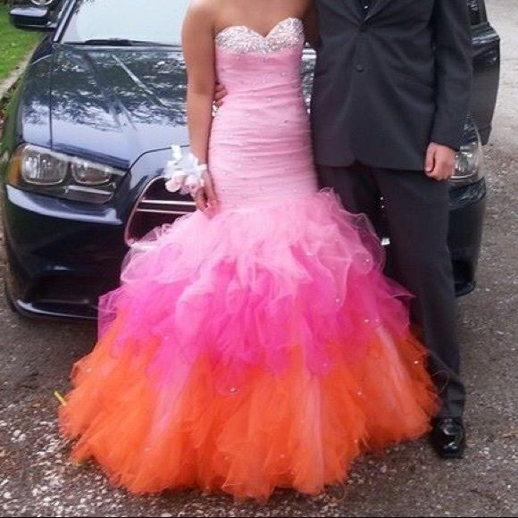 Pink Mori Lee prom dress! Long mermaid style dress with ombré bottom. Pink, hot pink, and orange. An original Mori Lee from peaches boutique in Chicago. It's a size 2 but I'm a 4 and it fits because it has a corset back! I went spray tanning before prom so it rubbed off on the inside of the dress but it it's only the inside! I'll include the original bag too, it's zebra print with green lining :) Mori Lee Dresses