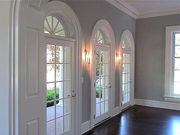 the white trim gray walls and dark wood floors love the dark door