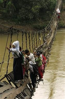 Students hold on to the side steel bars of a collapsed bridge as they cross a river to get to school in Sanghiang Tanjun