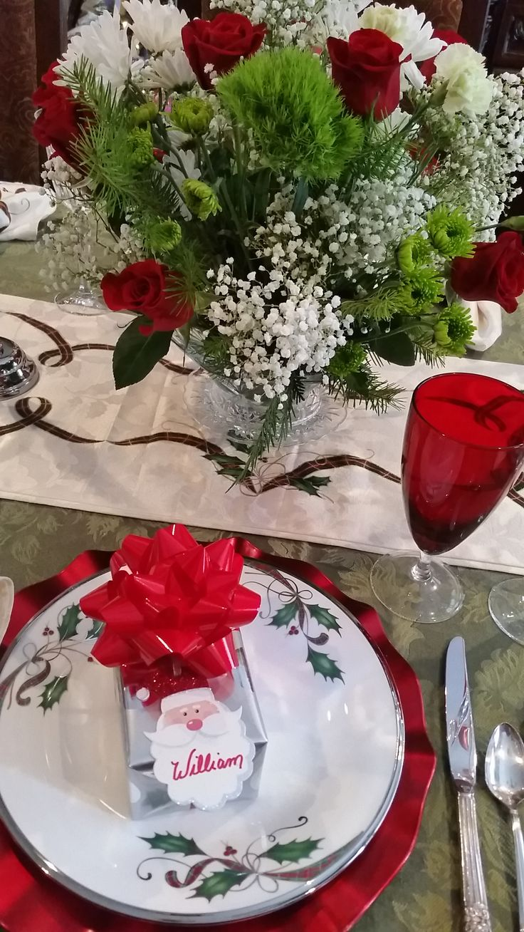 """Christmas 2017, 2 of 2, Green tablecloth with Lenox """"Holiday Nouveau Ribbon"""" runner and napkins and also china.  Red Lenox and Noritake crystal stems. Silver napkin rings and accents; small present at each setting also works as place card. Red scalloped chargers."""