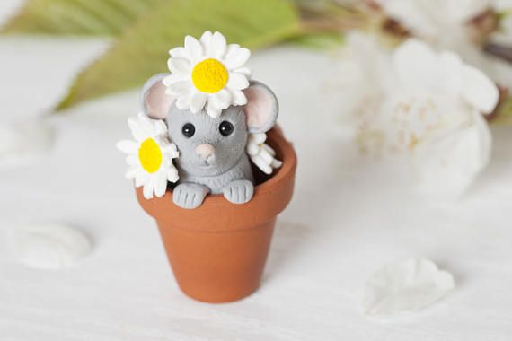 A happy mouse playing in a real terracotta pot among a lovely bunch of daises. The ornament measures approximately 4.5 cm (45 mm/1.7 inches) in height.  What a cute mouse popping it's head up with a cheeky smile while playing among daisies. Surrounded by individually handcrafted daisies the little mouse grasps the edge of the plant pot, smiling up at you while its tail curls out over the back. Your ornament will arrive in its own bespoke printed gift box.  Each piece is individually hand...