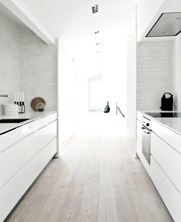 nice galley kitchen. white finger pull drawers. thin bench top. bagged brickwork splash back. limed oak floor boards. concealed range hood