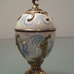 Very nice porcelain musical egg Fabergé with flowers on white background on gold base. The egg is in a beautiful rococo style. Good condition Size: 13.5 cm in height.