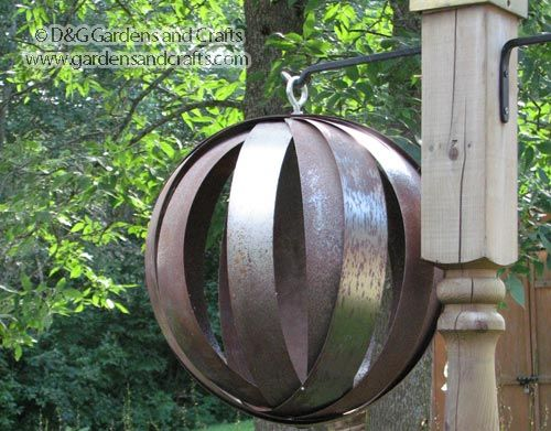 """""""These hanging garden spheres were made from the leftover spools from rolls of banding. Gary works in a lumber yard and they use banding to strap things down on pallets for shipping. The hoops already have a hole in them, so he lined up all the holes and put in an eye bolt to connect them, which is perfect for hanging them.""""   from http://www.gardensandcrafts.com"""