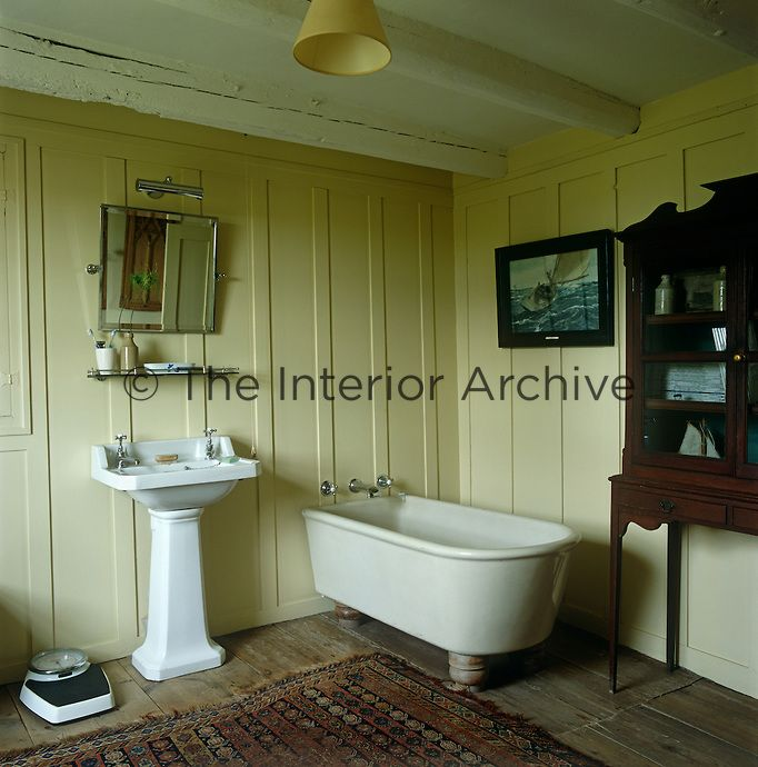 A wood-panelled bathroom with an old-fashioned pedestal basin, free-standing bath and antique cabinet creates a feeling of traditional English charm