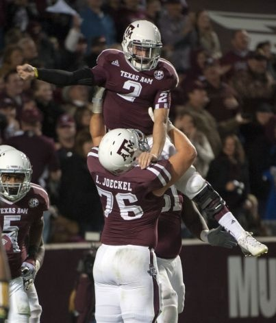 Texas A & M quarterback Johnny Manziel (2) gets a lift from Luke Joeckel (76) after running 18-yards for a touchdown during the third quarter of an NCAA college football game against Missouri, Saturday, Nov. 24, 2012, in College Station, Texas.  (Dave Einsel / Associated Press) / SA