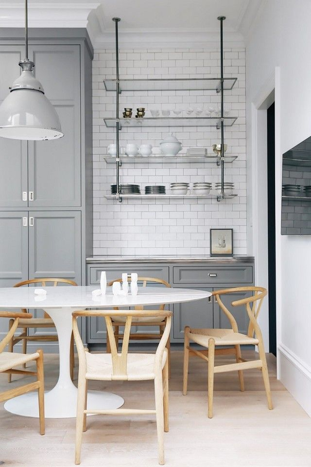 Industrial kitchen with subway tile, gray cabinents, a large industrial light, and wishbone chairs