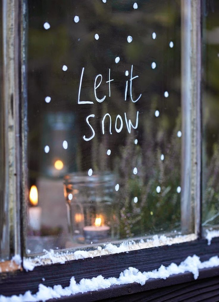 'Let It Snow' written on window in temporary white window marker - Decoist