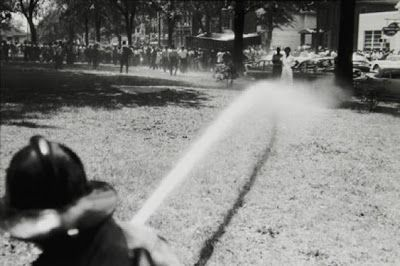 Firemen spray water at demonstrators, who are just out of reach during the Birmingham Campaign, 1963.  Photo credit: Bruce Davidson