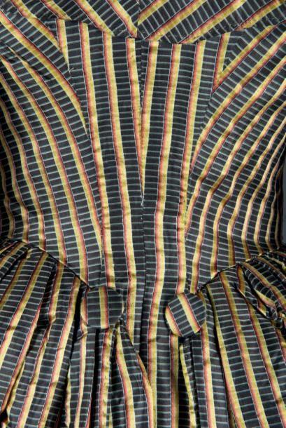 robe redingote, vers 1787. Satin de coton et soie gris charbon à bandes gris clair ponctué d'une rayure verticale en satin ombré jaune citron et rouge. Corsage baleiné à l'anglaise pour le dos, compères à double boutonnage. Double col ouvert formant capelette, manches longues coudées avec revers et gros boutons recouverts en pareil aux poignets (restes de dentelle blonde aux fuseaux). Jupe montée à petits plis serrés, 4 gros boutons ornementaux. Provenance: Famille du Pont de l'Oliverie