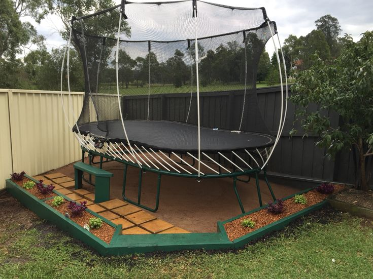 """This is what we did with our trampoline area. Garden boxes where the plants will form a hedge to """"hide"""" trampoline. Steps down onto stepping stones."""