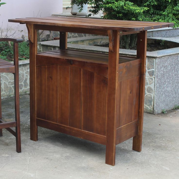 This light brown outdoor wooden table is the perfect spot to serve your guests drinks or an afternoon meal in style. The bar-style table is constructed of solid wood and features an exposed shelf and additional ones along the back for storage.
